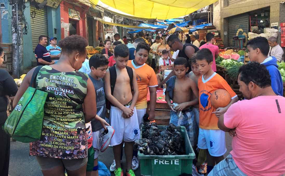 剛踢完足球的孩子們,在週日市集好奇地圍觀活螃蟹。圖/約客 提供